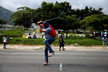 A demonstrator uses a golf club during a rally against Venezuelan President Nicolas Maduro's government in Caracas,