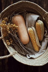 Top view on fresh healthy corn and pumpkin laying in straw rustic braided basket with linen textile and dried yellow flowers on dark wooden table background. Vertical atmospheric shot.