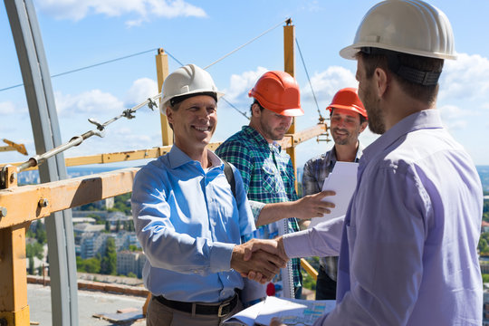 Builders Handshake, Two Happy Smiling Partners Shaking Hand After Meeting With Foreman Team On Building Construction Site