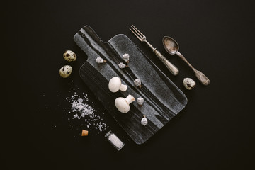 White raw champignon mushrooms on black marble cutting board with quail eggs, salt and silver cutlery on black background, top view