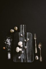 White raw champignon mushrooms on black marble serving board with quail eggs, salt and silver cutlery on black background, top vertical view