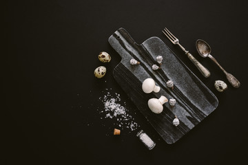White raw champignon mushrooms on black marble serving board with quail eggs, salt and silver cutlery on black background, top view