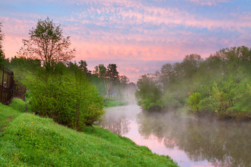 summer rural landscape with river, forest and fog at sunrise