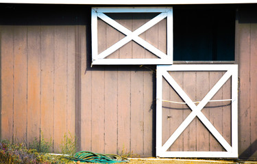 weathered  brown and white barn with dutch door