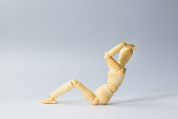 Wooden figure doll with sit up for health on white  for exercise training and helth concept