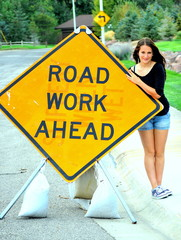 Female beauty posing at road work ahead sign.