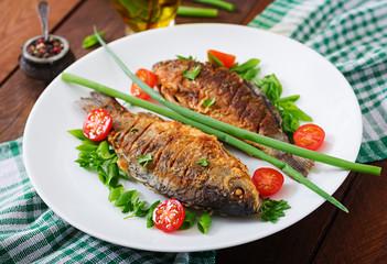 Foto op Textielframe Vis Fried fish carp and fresh vegetable salad on wooden background.