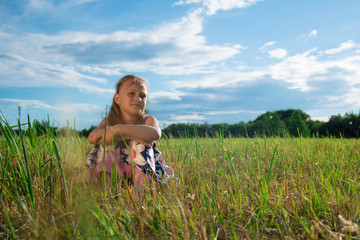 Portrait of a beautiful girl on grass in a park on a background of white clouds and blue sky