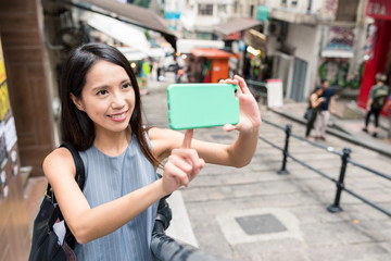 Woman taking photo with mobile phone in Pottinger Street