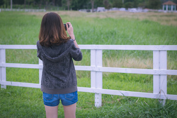 Young woman standing taking photo in a farm behind the fence. Cool tone.