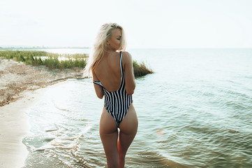 Shapely athletic healthy girl with a beautiful body and elastic buttocks on the beach