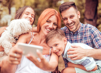 Happy family with dog taking selfie by smart phone in the park