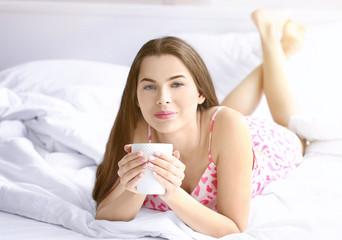 Beautiful woman drinking coffee on bed