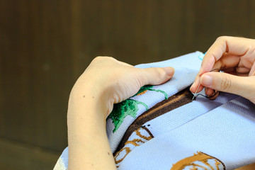 Young woman doing cross stitch at home. Close up of embroidery. Cross stitch is a hobby.