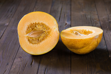 Melon cut in half on a wooden background
