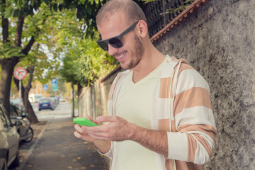Modern young man using cellphone on the street.