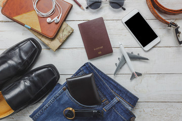 Top view men accessories to travel concept.White mobile  phone and headphone on wooden background.airplane,hat,passport,watch,sunglasses on wood table.
