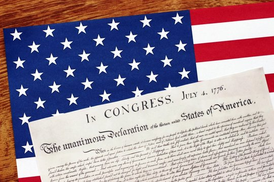 Declaration of Independence with American Flag on Wooden Table