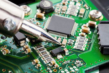 Close up studio shot of soldering iron and microcircuit