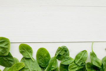 Spinach leaves on white wooden table top view