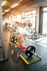 Full length portrait of healthy young man lifting weights in a gym.