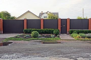 серо коричневый железный  забор перед асфальтированной дорогой с лужами