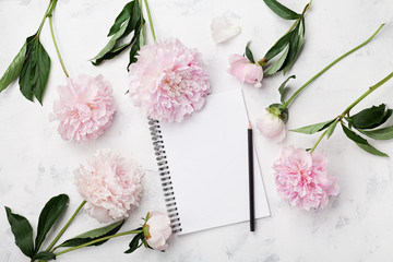 Empty notebook for wedding planning, pencil and pink peony flowers on white stone table top view in flat lay style. Woman working desk.