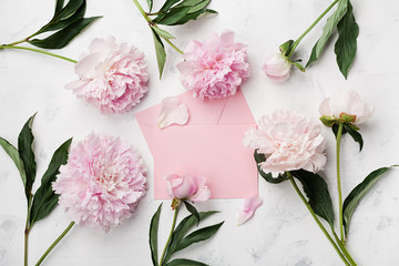 Pink peony flowers, envelope and paper card on white stone table top view in flat lay style.