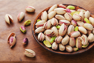 Bowl of pistachio nuts on wooden rustic table. Healthy food and snack.