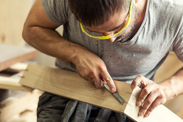 Obraz man treating a wooden product with a chisel - fototapety do salonu
