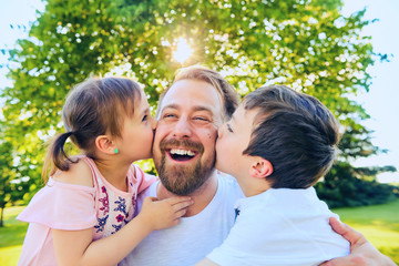 Little boy and girl kissing their happy father