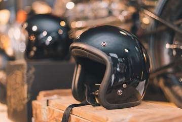 Fotorolgordijn Scooter Black glossy vintage helmet place on the wooden box in selective focus with vintage tone.