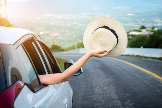 Relaxed happy traveler, Young beatiful asian gilr holding hat weave and Reach out of the car at sunset and beautiful view with mountain road background