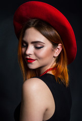 A woman in a red hat and a black dress. Fashion show concept