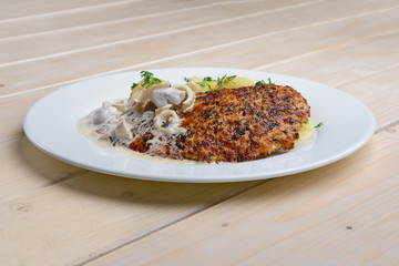 Fried chicken fillet in rosemary breading served with boiled potato and mushroom creamy sauce