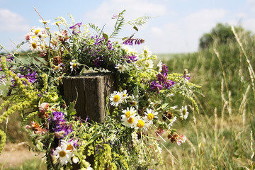 wreath of flowers hanging on a wooden stick on a wild field
