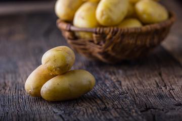 Fresh raw potatoes in basket on rustic oak board.