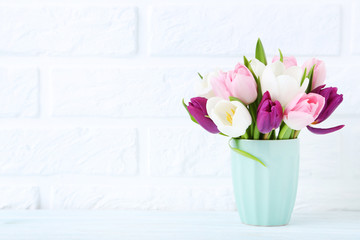 Bouquet of tulips in cup on brick wall background
