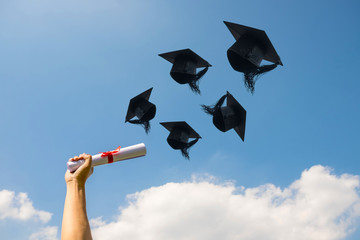 Graduation day, Images of hand holding a certificate and Caps or hat throwing in the air with sunshine day on blue sky background, Happiness feeling, Commencement day, Congratulation, Ceremony