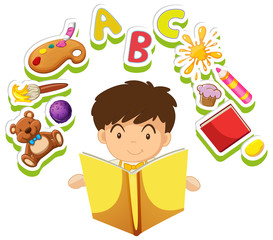 Boy reading book with toys in background