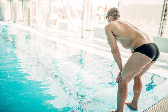 Athletic male swimmer sits on the curb, back view
