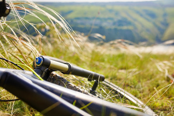 Close-up of detail of the mountain bicycle on the green grass.