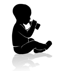 Silhouette baby sitting drinking from baby bottle