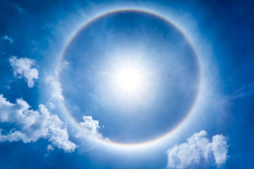 The storng sun halo at noon time on the blue sky and cumulus clouds
