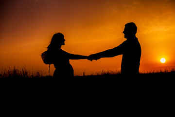 Silhouette of Happy Young Couple love Outside at Sunset. Young couple enjoying the sunset in the meadow