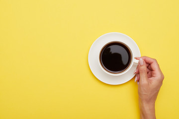 Flat lay of cup of delicious coffee in woman hand