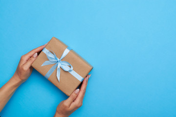 Flat lay of hands of female placing a present box on background