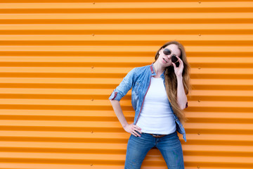 redhead girl in jeans shirt with sunglasses near orange wall