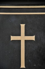 Detail of cross on tombstone in cemetery. Engraving with christian religious symbol in close up with copy space