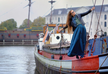 Portrait of a girl, model by the ship in the port. Fashion, style, beauty.
